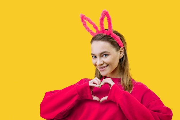 Smiling young caucasian woman, blonde with pink bunny ears, shows a heart with two hands and looking at camera isolated over yellow background