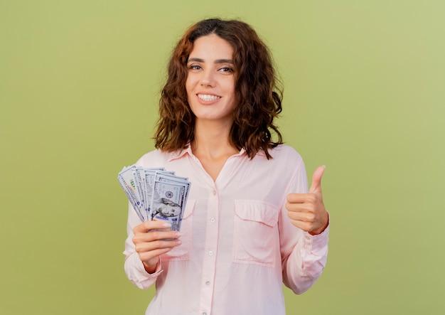 Улыбающаяся молодая кавказская женщина держит деньги и большие пальцы руки вверх изолирована на зеленом фоне с копией пространства