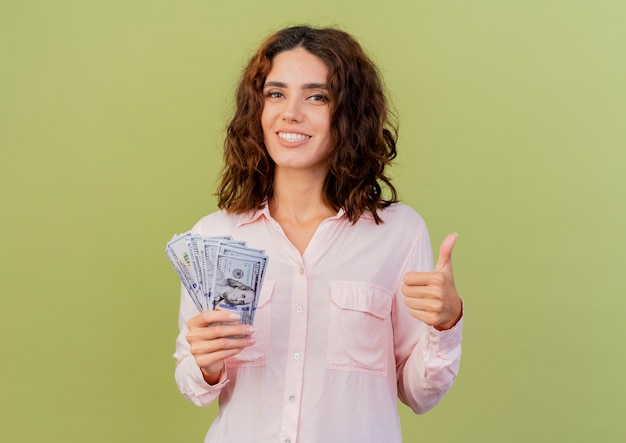 Smiling young caucasian woman holds money and thumbs up isolated on green background with copy space