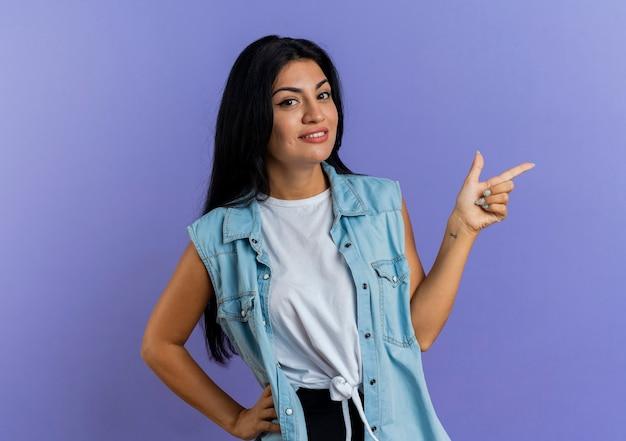 La giovane donna caucasica sorridente indica al lato isolato su fondo viola con lo spazio della copia