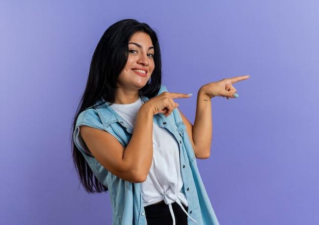 Sorridente giovane donna caucasica punti a lato con due mani che guarda l'obbiettivo isolato su sfondo viola con spazio di copia