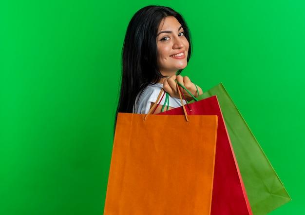 Улыбающаяся молодая кавказская женщина стоит боком, держа бумажные хозяйственные сумки, изолированные на зеленом фоне с копией пространства