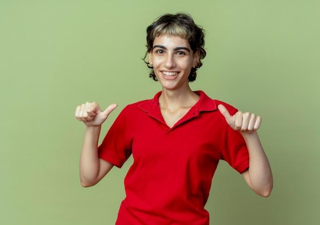 オリーブグリーンで隔離の親指を示すピクシーヘアカットと笑顔の若い白人女性