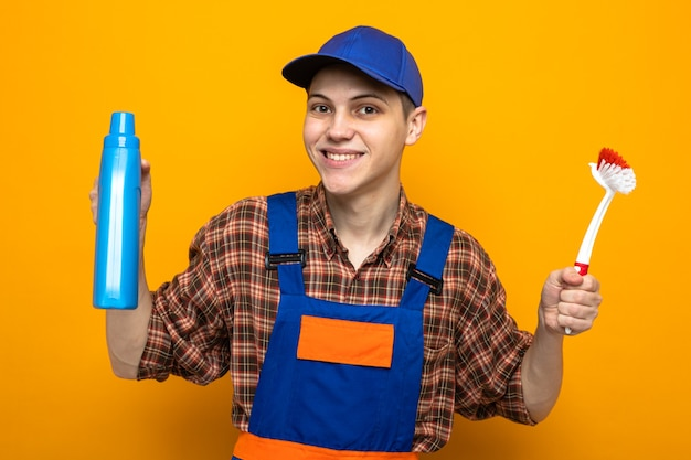 Smiling young cleaning guy wearing uniform and cap holding cleaning agent with brush