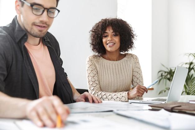 Улыбающиеся молодые коллеги читают документы, сидя за столом в офисе