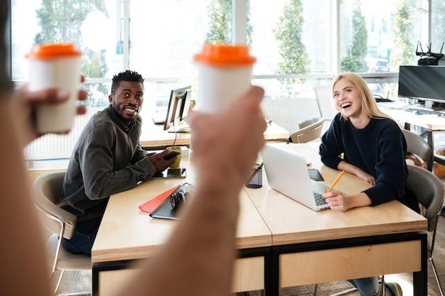 オフィスのコワーキングに座っている笑顔の若い同僚