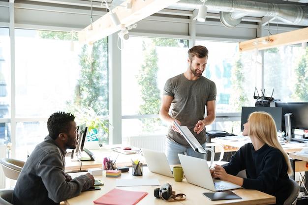 Giovani colleghi sorridenti che si siedono nel coworking dell'ufficio