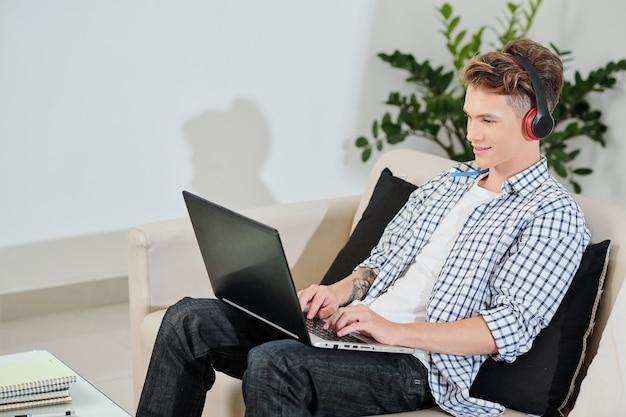 코딩하거나 집에서 랩톱에서 재생할 때 헤드폰을 착용하는 젊은 대학생 미소