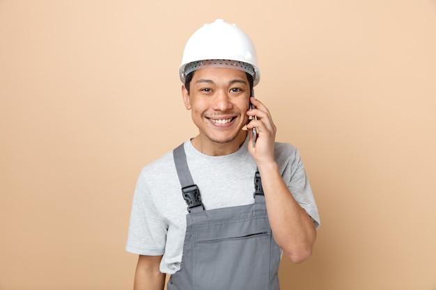 安全ヘルメットと電話で話している制服を着て笑顔の若い建設労働者