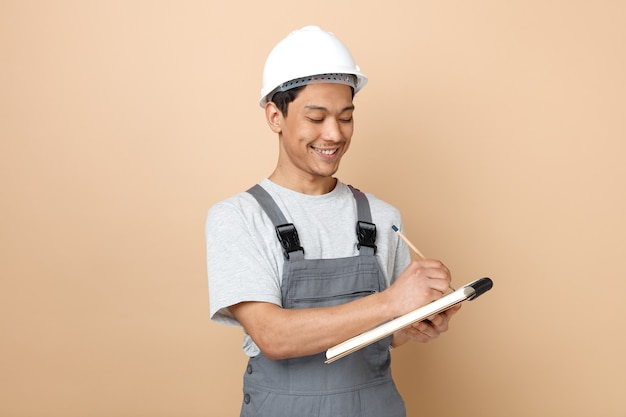 메모장에 연필로 안전 헬멧과 유니폼 쓰기를 입고 웃는 젊은 건설 노동자