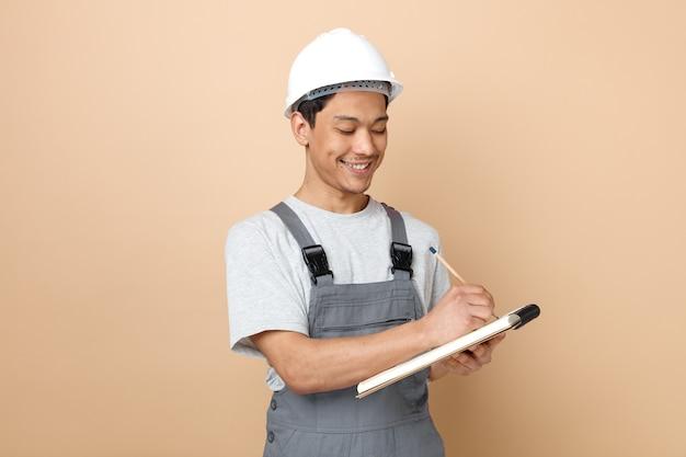 Sorridente giovane operaio edile che indossa il casco di sicurezza e scrittura uniforme con la matita sul blocco note