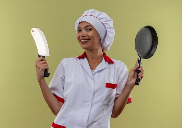 包丁とフライパンを保持しているシェフの制服を着て笑顔の若い料理人の女性