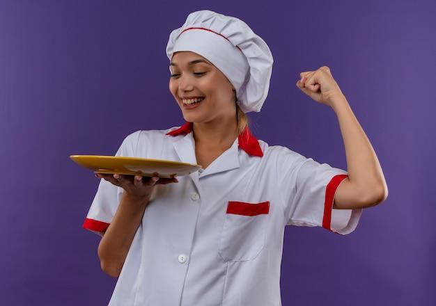 コピースペースと孤立した背景にyesジェスチャーを示すシェフの制服保持プレートを身に着けている若い料理人女性の笑顔