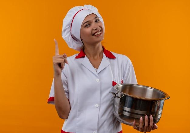 鍋を保持しているシェフの制服を着て笑顔の若い料理人の女性は、コピースペースで孤立したオレンジ色の背景に指を指しています