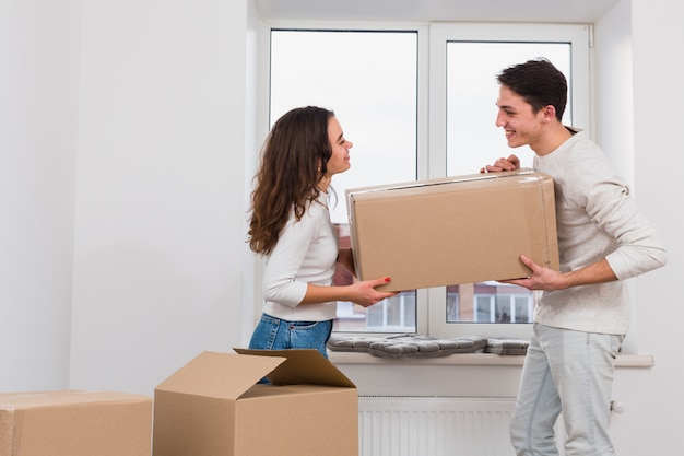 Smiling young couple carrying cardboard box in new apartment