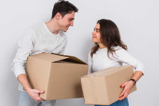 Smiling young couple carrying cardboard boxes in hand looking at each other against white background