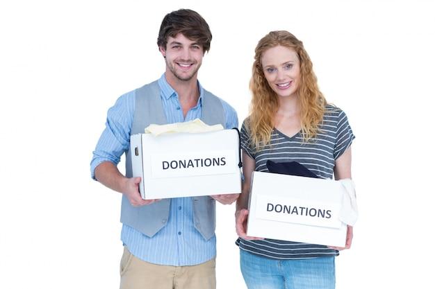 Улыбаясь молодая пара с коробкой для пожертвований
