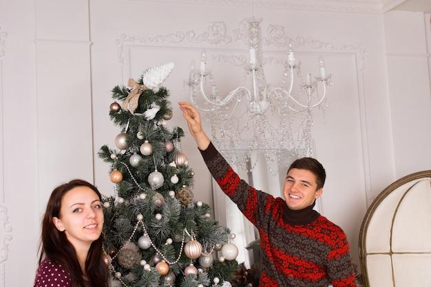 カメラに微笑んでクリスマスツリーに最後の仕上げを置くクリスマスのために飾る笑顔の若いカップル