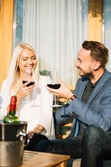 一緒に飲み物を楽しむ若いカップルに笑顔