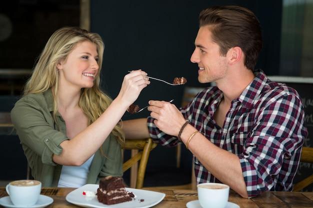 カフェでお互いにデザートを食べている若いカップルの笑顔