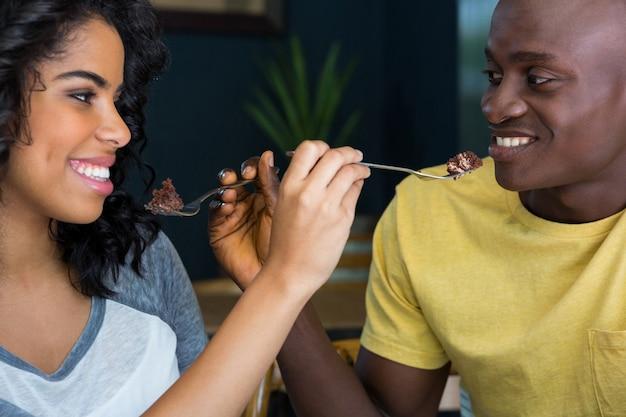 コーヒーショップでお互いにデザートを食べている若いカップルの笑顔