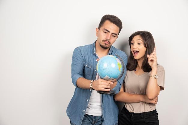 Sorridente giovane coppia amici uomo e donna alla ricerca sul globo terrestre.