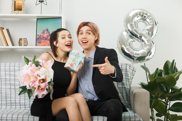 Sorridente giovane coppia in felice giornata delle donne che tiene e indica il bouquet e il presente seduto sul divano nel soggiorno