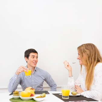 Smiling young couple having healthy breakfast