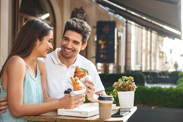 屋外のカフェに座って昼食をとっている若いカップルの笑顔