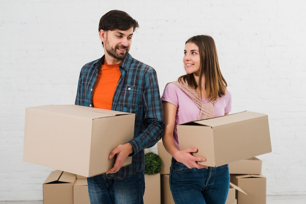 Smiling young couple holding cardboard boxes in hand looking at each other