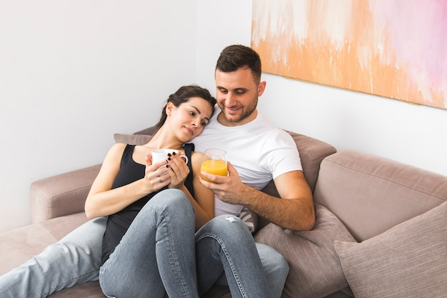 Smiling young couple holding coffee cup and juice glass on sofa