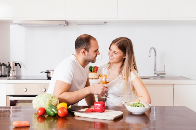 Smiling young couple holding glasses of wine looking at each other