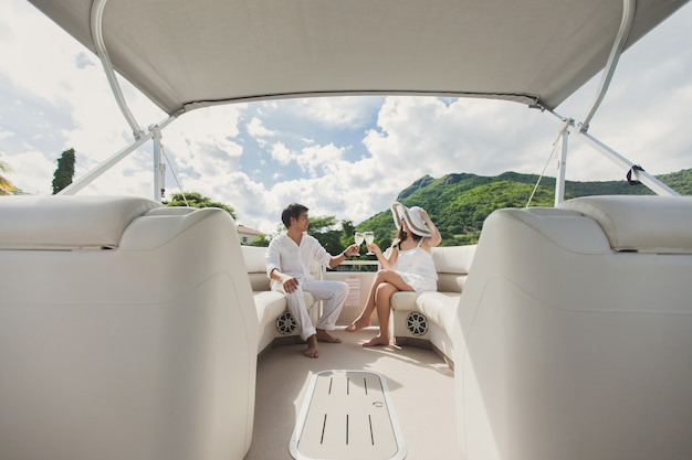 Smiling young couple holding glasses with champagne and looking at each other while sitting on the board of yacht
