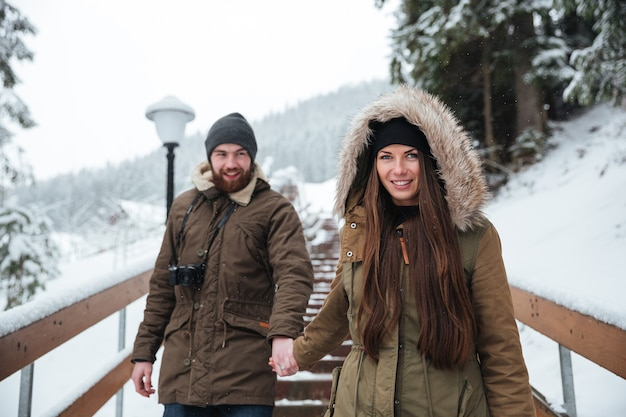 Smiling young couple holding hand and walking on stairs in winter mountains