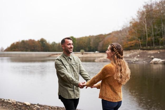 湖で手をつないで笑顔の若いカップル