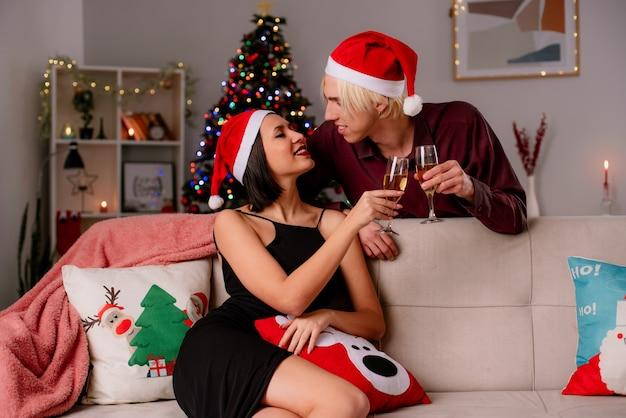 Sorridente giovane coppia a casa nel periodo natalizio indossando santa cappello tenendo un bicchiere di champagne