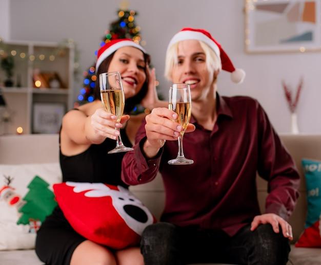 Sorridente coppia giovane a casa durante il periodo natalizio indossando il cappello della santa seduto sul divano nel soggiorno allungando un bicchiere di champagne con cuscino di natale sulle gambe