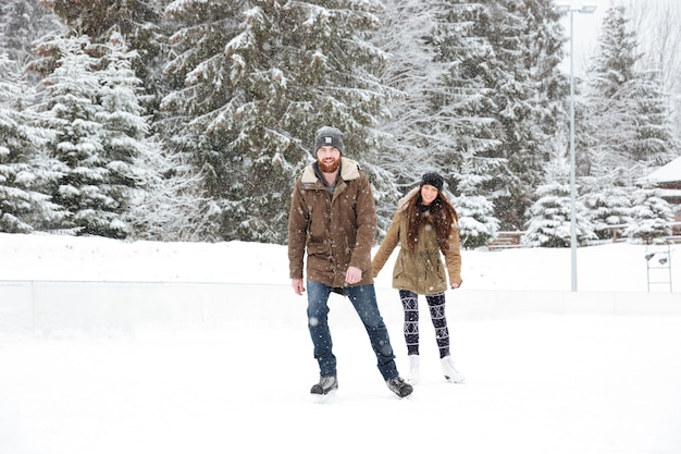 Smiling young couple ice skating outdoors with snow