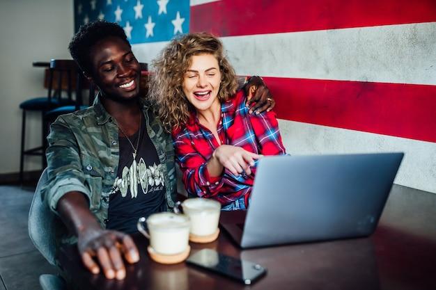 タッチスクリーンコンピュータを使用してコーヒーショップで若いカップルの笑顔。デジタルタブレットを見ているレストランで若い男性と女性。