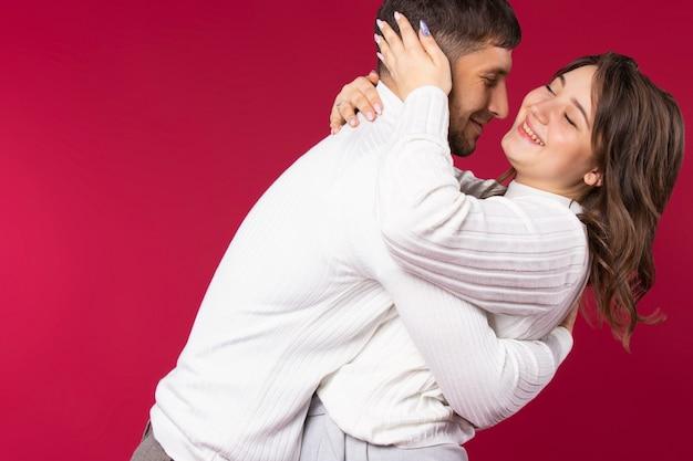 빈 쪽 공간이 빨간색 배경에 포용하는 사랑에 젊은 부부 미소.