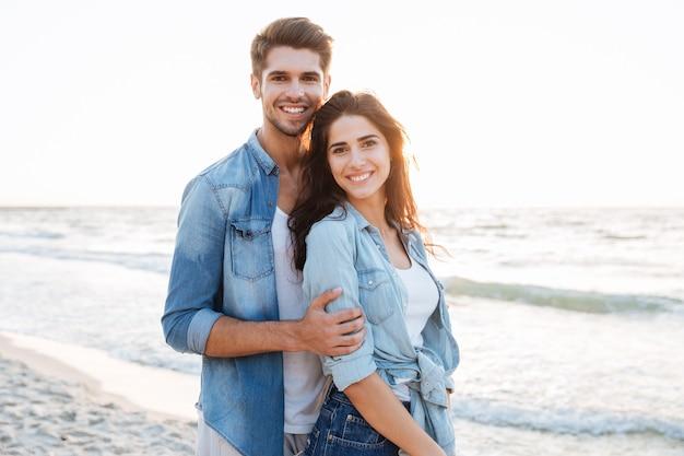 Улыбаясь молодая влюбленная пара, стоя на пляже