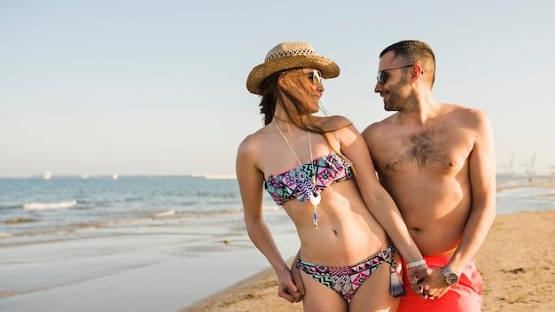 ビーチでお互いの立っているを見ている水着で笑顔の若いカップル