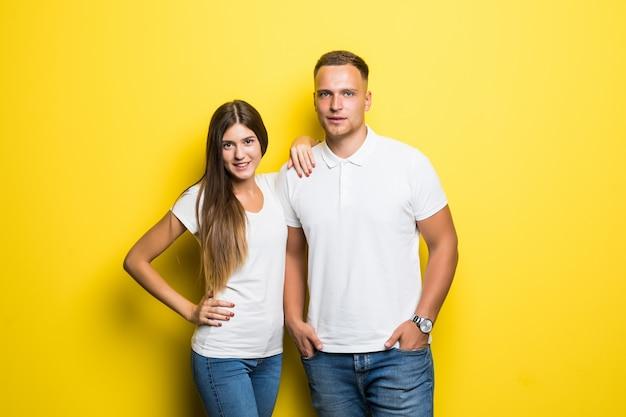 Sorridente giovane coppia isolata su sfondo giallo che abbracciano insieme vestiti in magliette bianche