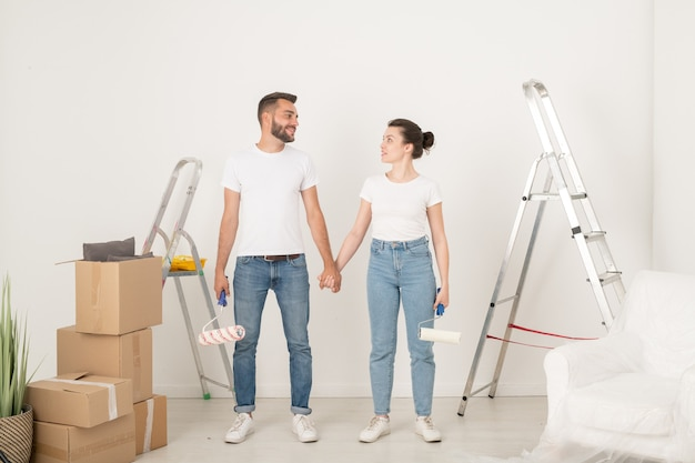 Smiling young couple in jeans holding hands and looking at each other while supporting each other during remodeling room