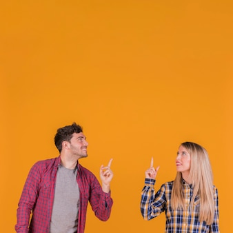 Smiling young couple looking up and pointing their finger upward against an orange background