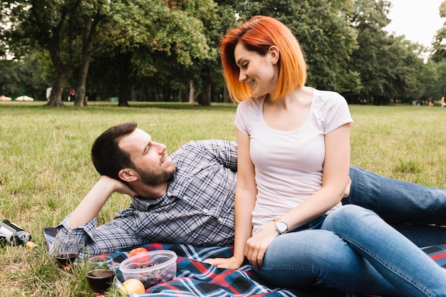 Smiling young couple lying on blanket over green grass with many fruits