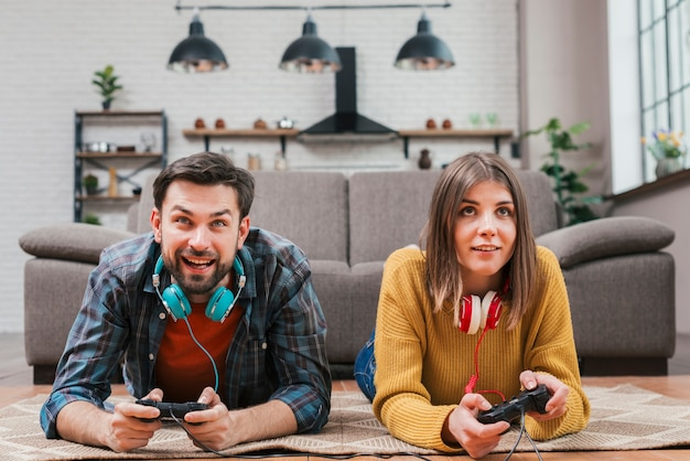 Smiling young couple lying on floor playing the video game with joystick at home