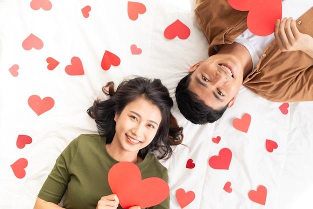 多くのハートの形でベッドに横たわって笑顔の若いカップル。