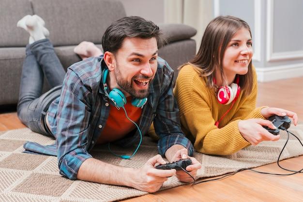 Улыбающаяся молодая пара лежит на полу и играет в видеоигру с джойстиком у себя дома