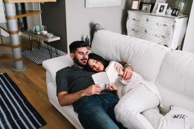 Smiling young couple lying on sofa reading book in living room